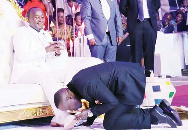 Photos: Ugandan pastor, Prophet Elvis Mbonye sits on white and gold throne as worshippers kiss his shoes