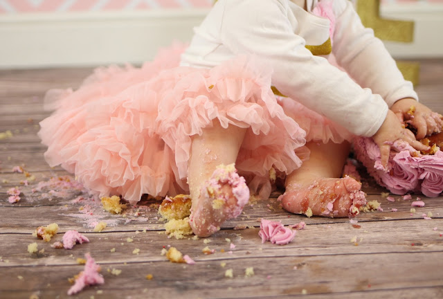 close up of messy baby feet at cake smash on wooden floor