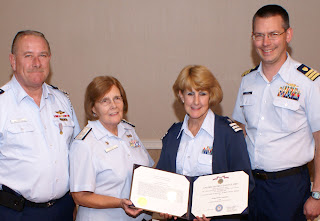 Helen Cummings receives Achievement Medal from Auxiliary and Coast Guard leaders.