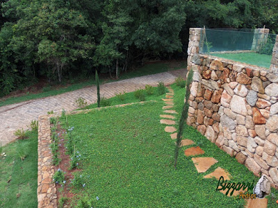 Execução do caminho no jardim com pedra Goiás tipo cacão com juntas de grama com execução do calçamento de pedra com pedra folheta em sítio em Piracaia-SP.