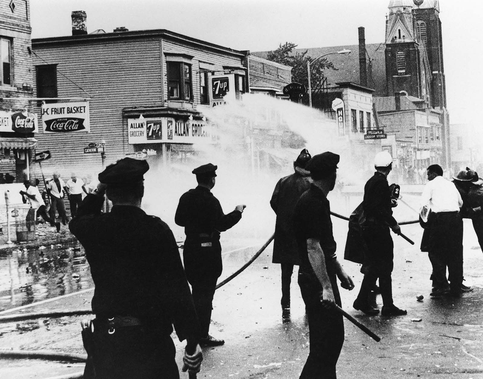 New York firemen, backed up by police, turn fire hoses on rioters in Rochester, New York, on July 25, 1964 in an effort to quell street disturbance. Set off by reports of police brutality during an arrest on July 24, the Rochester riot lasted several days.