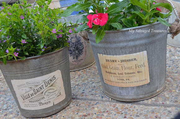 Two galvanized tubs decorated with printable labels and filled with flowers