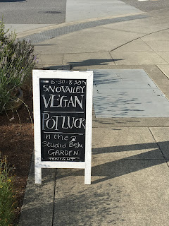 Photo of an A-Board sign on a sidewalk indicating the Sno-Valley Vegan Potluck in the Studio Beju garden. https://trimazing.com/