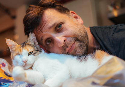 man cuddling tortie and white cat with one eye