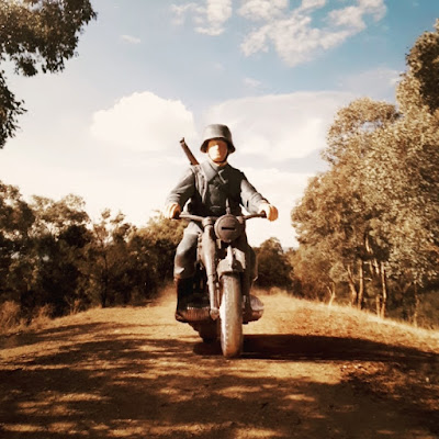 Model toy soldier riding a motorbike down a dirt road in an Australian bush setting.