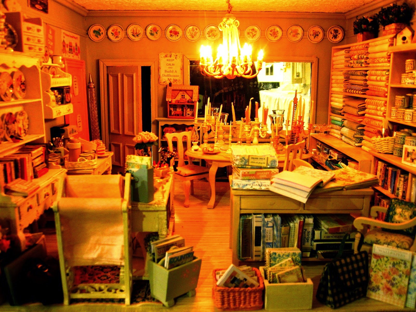 Ground floor of a modern miniature shabby chic shop, with a counter to the left, a dining table covered in candlesticks in the centre, wallpaper books to the back, fabric and paint on the right.