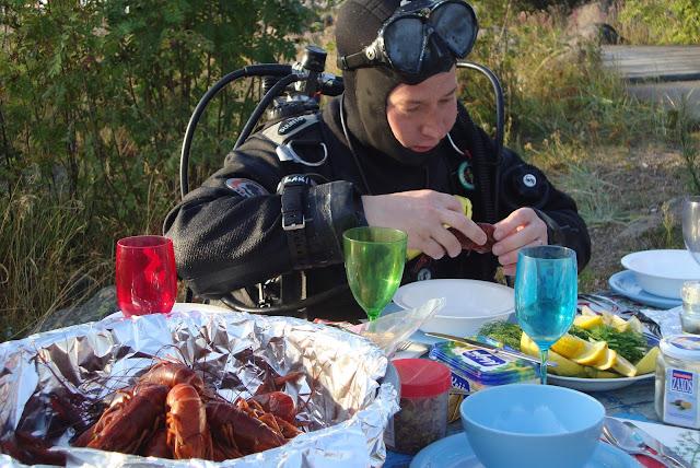 Sukelluspukuinen henkilö istuu ruokapöydässä, jossa on tarjolla rapuja