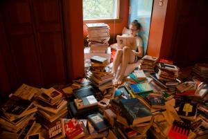 A imagem mostra uma menina que lê um livro, cercada por pilhas e por pilhas de outros livros.