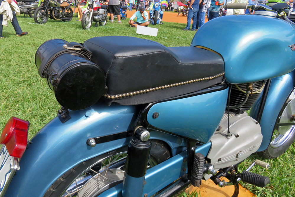 Round tool box attached to rear of seat.