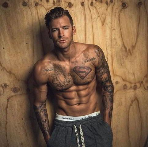 Chico posando de pie, lleva tatuaje de superman en el pectoral