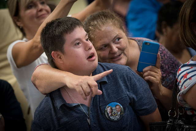 a young white man with Down Syndrome stands in the crowd with a look of anticipation on his face and sporting a Clinton-Kaine button on his shirt; an older woman, presumably his mother, stands beside him, her arm around his neck, gesturing toward Hillary