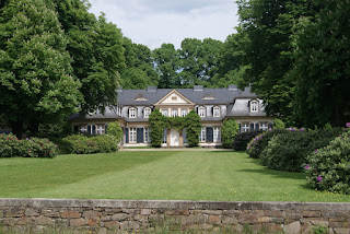 Ein cremefarbenes, herrschaftliches Wohnhaus am Ende einer großen, gepflegten Wiese