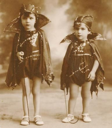 Vintage photo early 1900s. Two cute children dressed as devils in sparkly handmade costumes including capes and caps. Redbad Standards and Other Stories of Hell. marchmatron.com