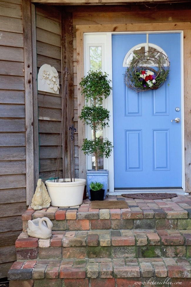 front brick porch with live floral grapevine wreath on blue front door and topiary plant