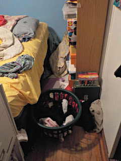 A messy room with clothes on the floor.