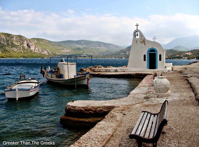 A typically Greek, whitewashed church,  on the shores of Lake Vouliagmeni, Loutraki, Greece.