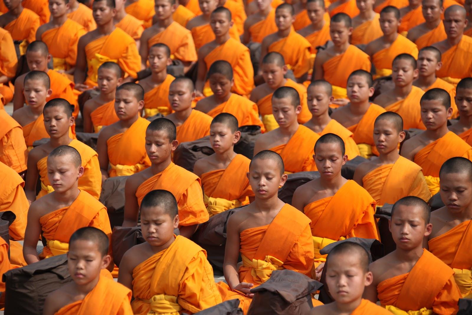オレンジの僧衣を着て瞑想するタイ人の仏教徒たち