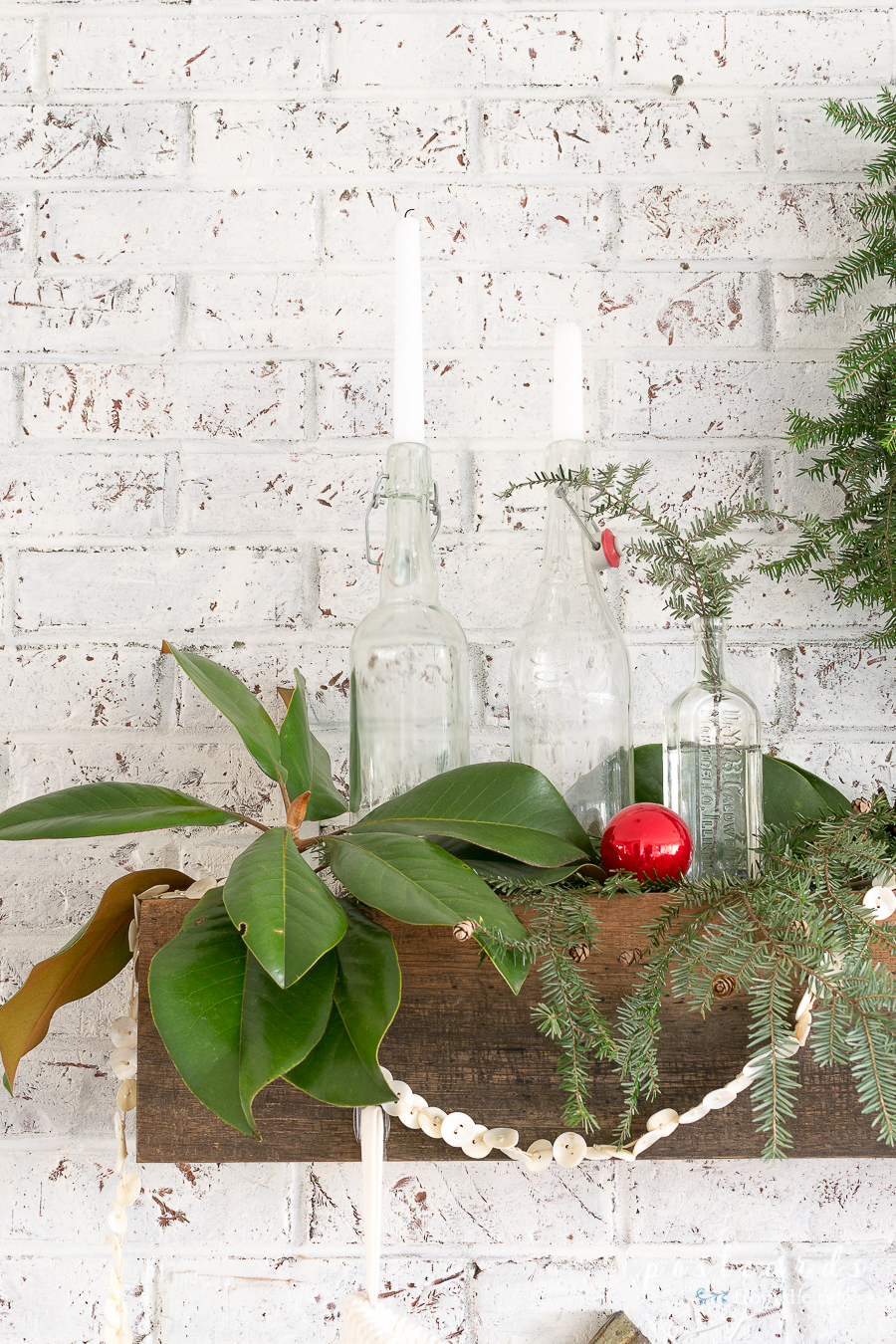 fireplace mantel shelf with magnolia branches and Christmas decor