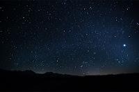 Gece ufuktaki karlı dağlar üzerindeki yıldızlı gökyüzü