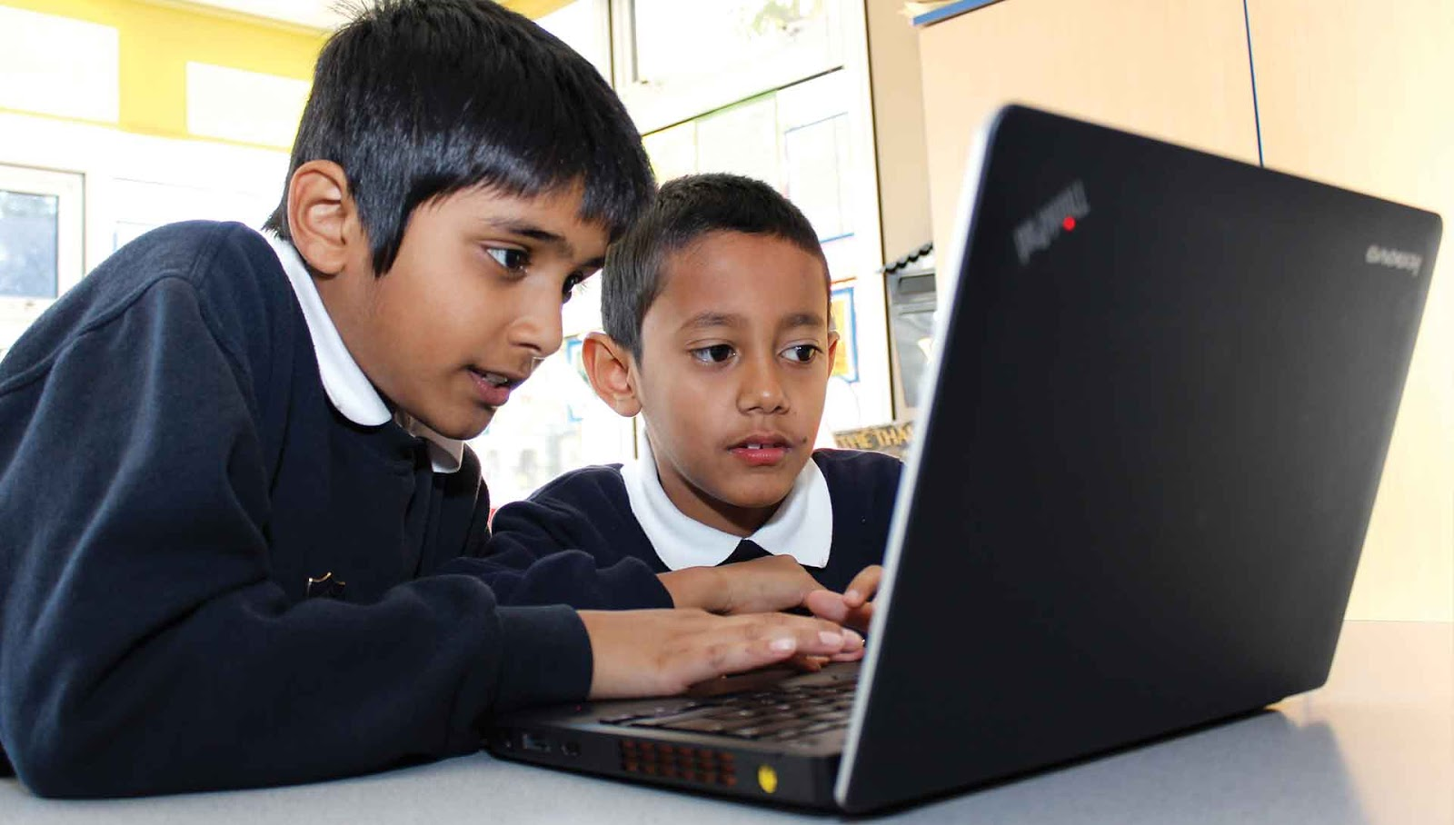 [Image: two-children-working-on-computer.jpg]