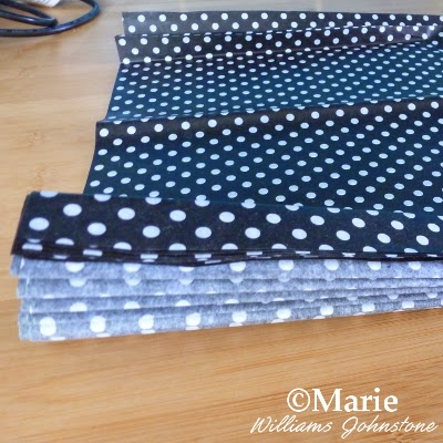 black polka dot tissue paper being folded up for a decorative craft