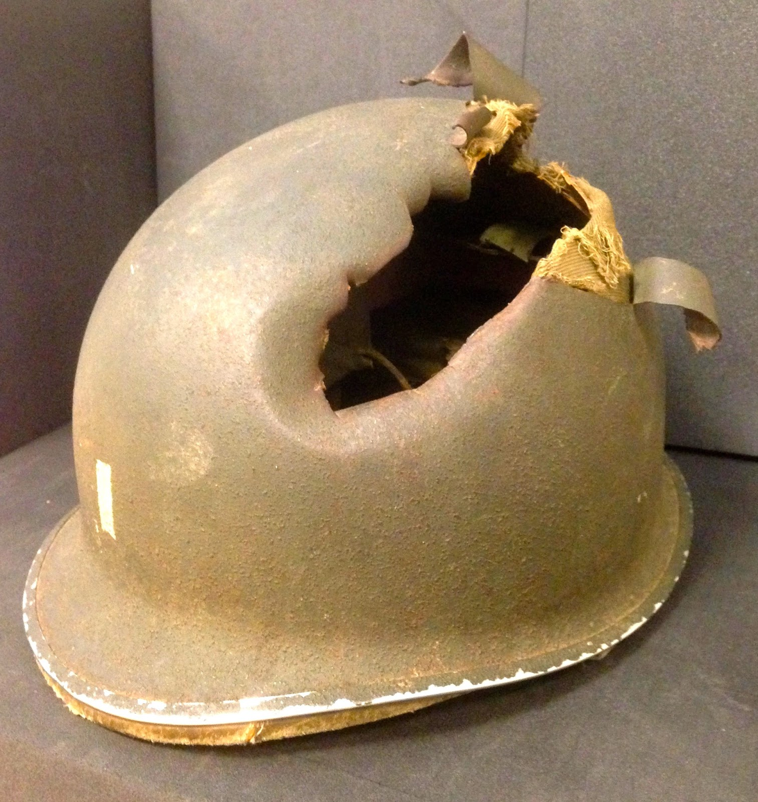 A helmet with a gaping rip in its top.