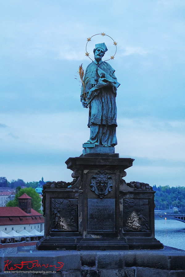 The statue of John of Nepomuk before dawn. The Charles Bridge in Spring Prague by Travel and Lifestyle Photographer Kent Johnson.