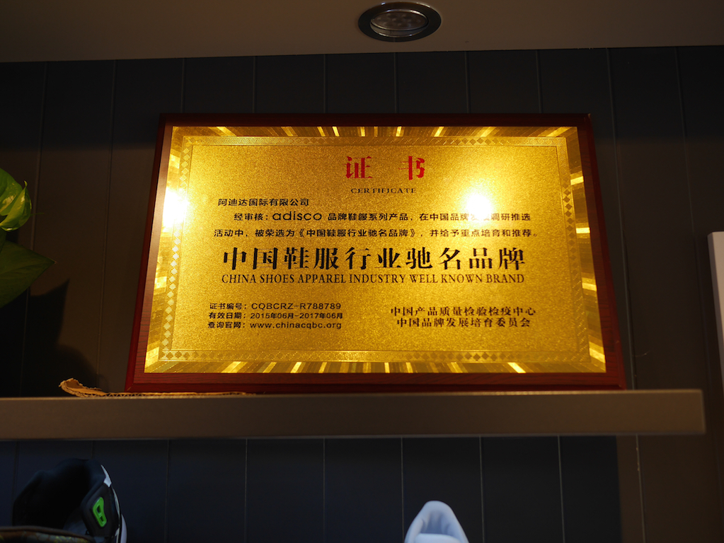 """Gold plaque proclaiming Adisco is a """"China Shoes Apparel Industry Well Known Brand"""""""