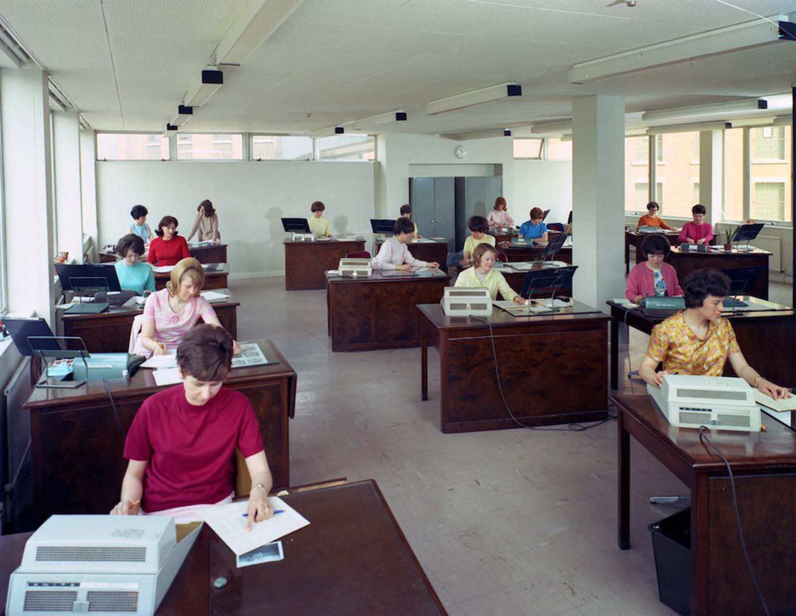 Administration office at Huntsman House, headquarters of Tetley's brewers in Leeds, West Yorkshire. Women workers use Sumlock machines, forerunners of the calculator. They wear clothes in a palette of bright colours. Of the 17 women in the picture, four wear pastel yellow, three wear pastel pink, two wear pastel blue. The women have a wide variety of hair styles, most strongly volumized with hairspray. 1968.