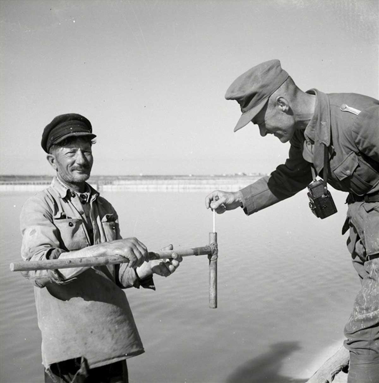 Un soldado de la Wehrmacht con un pescador local.