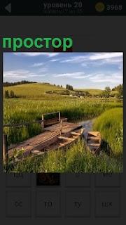 На фотографии речка, мост, лодка и бескрайние поля. Обширное пространство