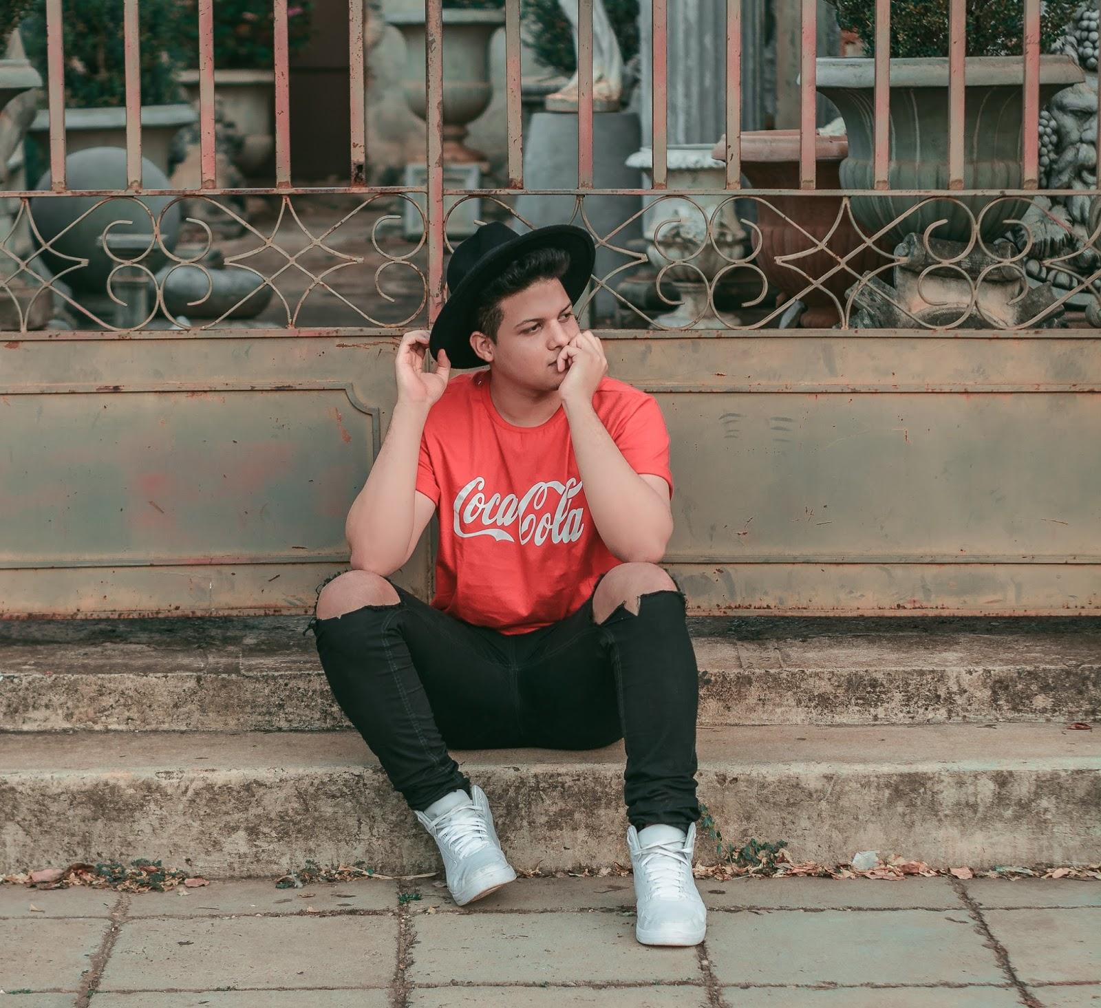 Look Masculino com Calça Preta Destroyed, Tênis Branco, Camiseta Vermelha e Chapéu Fedora Preto