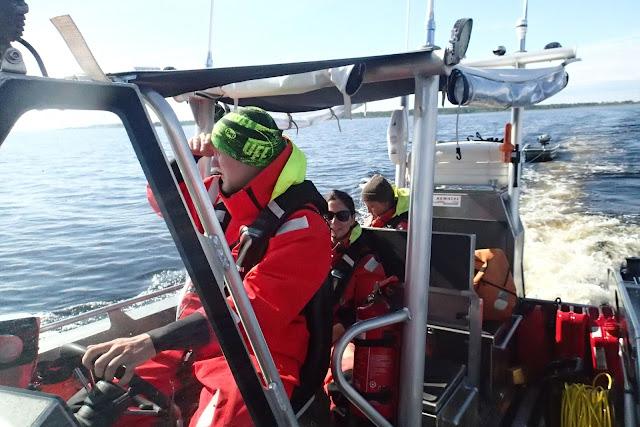3 ihmistä veneessä, kippari tähystää horisonttiin.