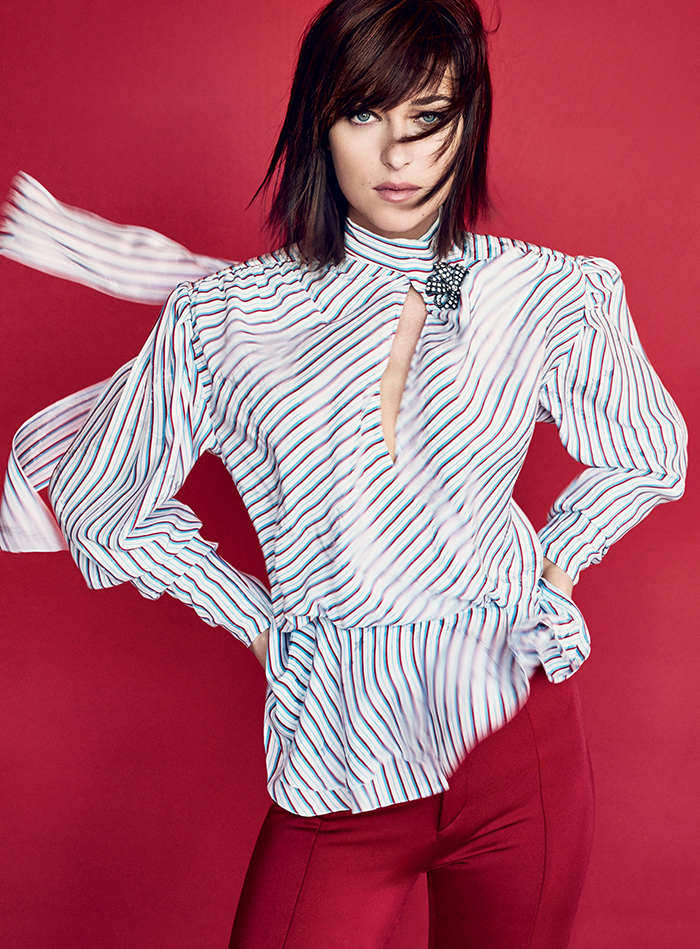 Image of hollywood actress dakota johnson wearing a striped shirt and red trousers for a photoshoot