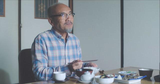 Vemos al protagonista Takeshi Kasumi (Naoto Takenaka) feliz comiendo arroz, lleva una camisa de cuadros