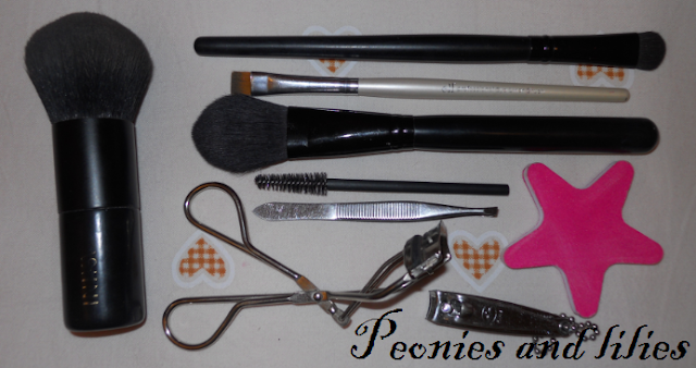 Inika kabuki brush, Elf studio eyeshadow c brush, Elf eyeliner brush, Elf blush brush, Disposable mascara wand, Tweezers, Eyelash curlers, Nail clippers, Nail file, What's in my travel make up bag
