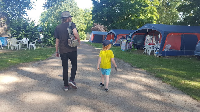 Man and child walking in campsite sunshine