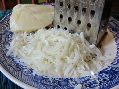 Grating homemade goats milk mozzarella.