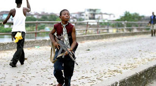 A Liberian child soldier fighting for Charles Taylor's government forces during the civil war in Monrovia, Liberia, July 30, 2003