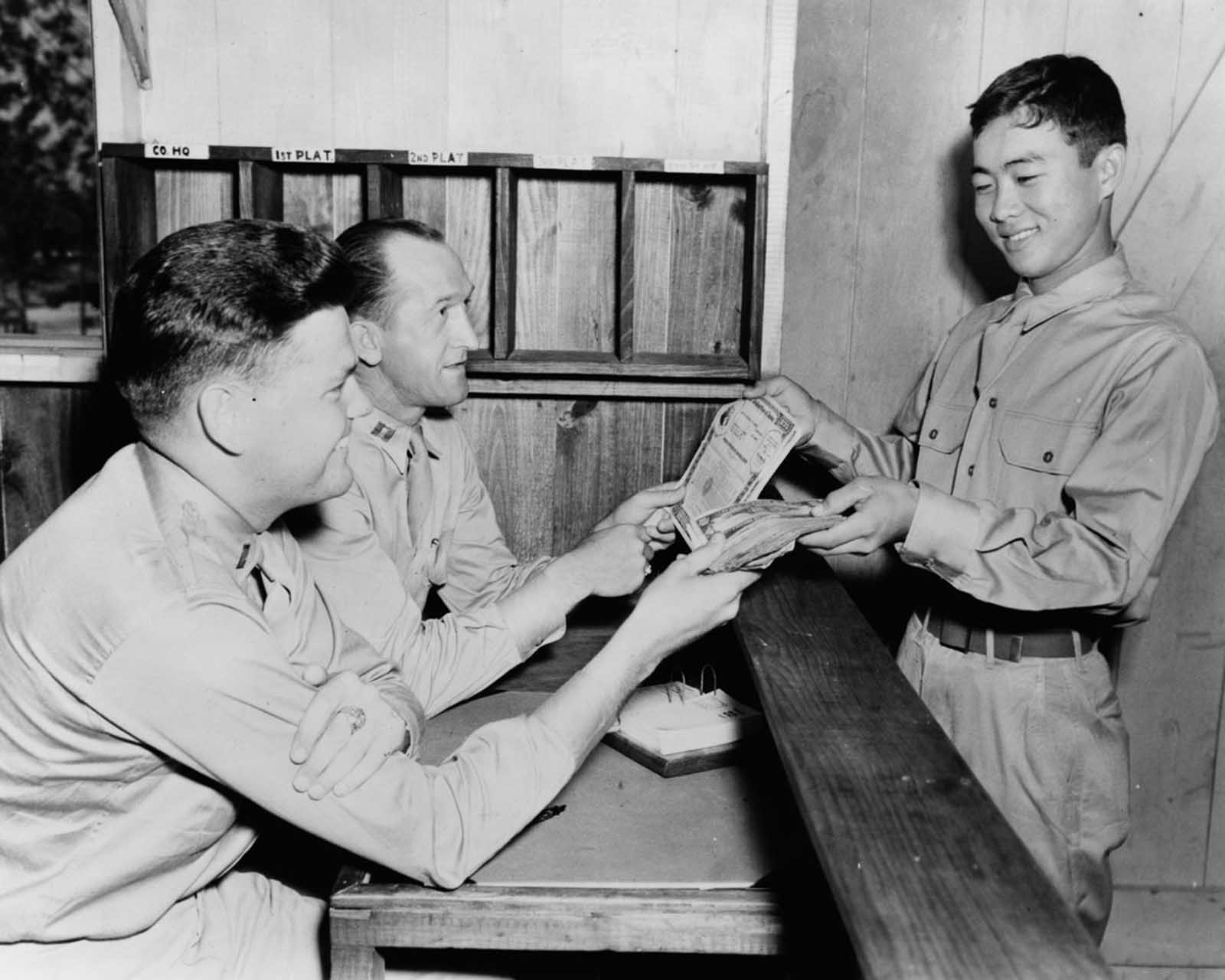 Private Jack Y. Oato purchases $2,500 worth of war bonds from his company commander. June, 1943.