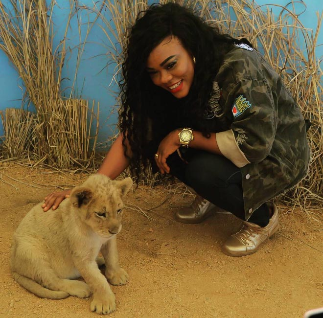 Actress Daniella Okeke plays with lion on United States trip