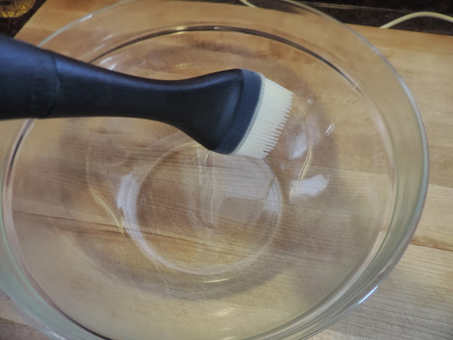 A mixing bowl being brushed with oil.