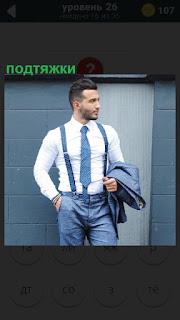 Стоит мужчина, пиджак в руках и подтяжки на теле поддерживают брюки