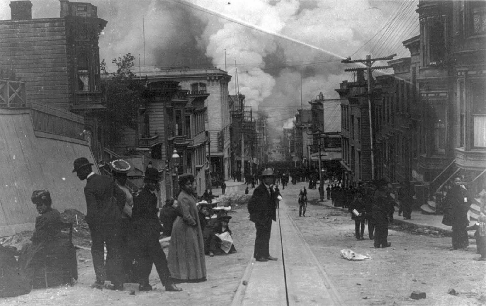 African American families on street during the San Francisco Fire of 1906, with clouds of smoke billowing at bottom of hill in background.
