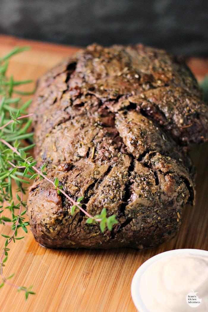 Whole, cooked Garlic Herb Beef Tenderloin Roast with Creamy Horseradish Sauce | by Renee's Kitchen Adventures on cutting board with fresh rosemary garnish