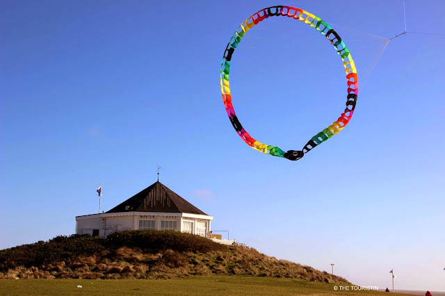 A white pavilion by the sea under a blue sky, a colourful kite flying overhead.