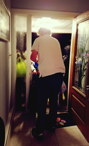 image of Iain standing at the front door handing out Halloween candy to trick-or-treaters