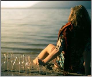 Chica joven sentada en la playa, mirando al mar, mientras que agarra una botella de cristal vacía, junto a muchas más.