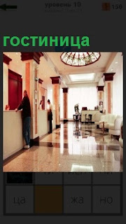 Холл гостиницы, где около регистратуры стоят люди для оформления