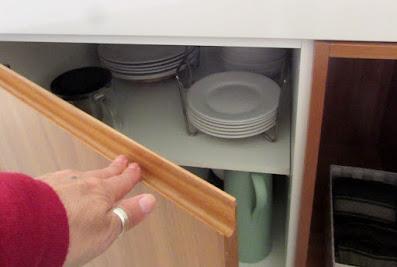 mão abrindo porta de armário de cozinha